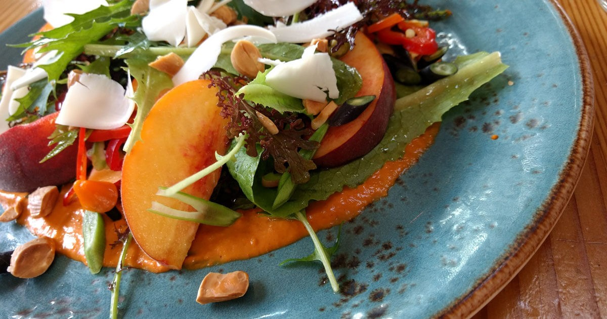 Romesco sauce, sweet peaches and peppers, almonds, greens and aged goat.