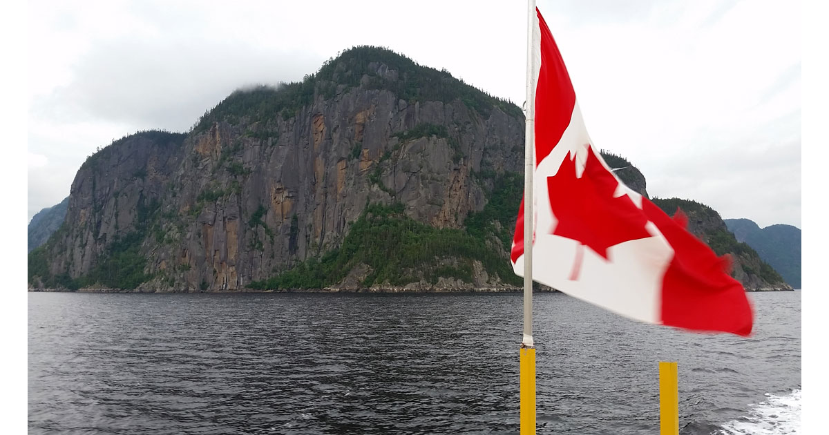 Cap Trinite from the water of Saguenay Fjord with Canadian flag in foreground